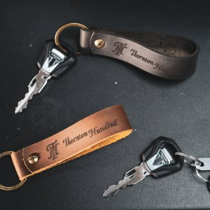 a picture of a black leather hagkeyring and a brown leather tag keyring