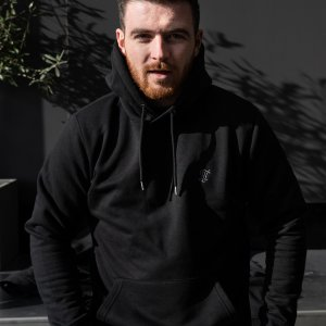 Model wearing a black jumper with a subtle logo on the jumper