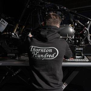 "model wearing a bold print hoodie, picture shows the back of a hoodie with writing ""Thornton Hundred Motorcycles"" on the jumper"