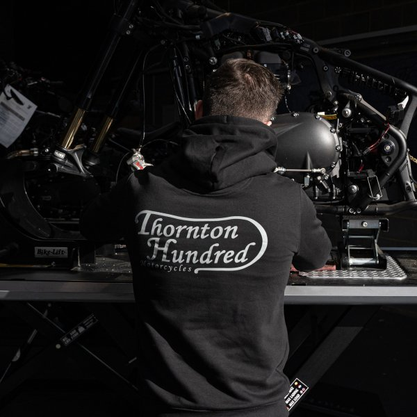 """model wearing a bold print hoodie, picture shows the back of a hoodie with writing """"Thornton Hundred Motorcycles"""" on the jumper"""