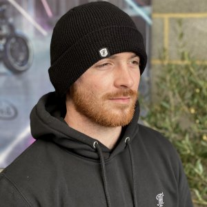 Picture shows a person wearing a black waffle beanie with a TH logo stitched on the side