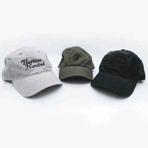 a picture of three TH embroiled caps with Thornton Hundred embroiled on the caps. the colours of the caps are light grey, olive green and black