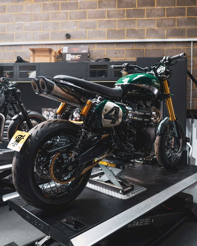 A picture of a green Triumph Scrambler supermoto custom designed by Thornton Hundred Motorcycle