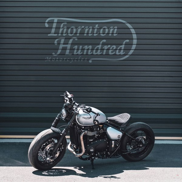 A picture of a Thornton Hundred Motorcycle outside a garage sat in the sun with the Thornton Hundred Motorcycle logo on the wall in the background